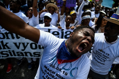Activists and students raise placards and shout slogans during a protest against the increased number of rapes and violence against women, May 26, 2019 in Port-au-Prince.
