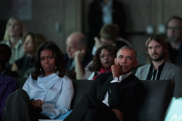 **FILE** Former first Lady Michelle and former president Barack Obama listen to speakers at the inaugural Obama Foundation Summit in Chicago on Oct. 31, 2017. The two-day event will feature a mix of community leaders politicians and artists exploring creative solutions to common problems, and experiencing art, technology, and music from around the world. (Scott Olson/Getty Images)