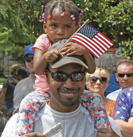 A father carries his daughter on his shoulders as they take in the sights during the 2019 Memorial Day Parade in northwest D.C. (Roy Lewis/The Washington Informer)
