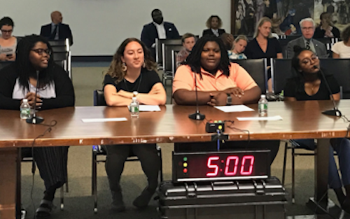 Hannah Dunn (Wilson High School), student representatives Tatiana Robinson (Ballou Senior High School) and Marjoury Alicea (Capital City Public Charter School), and Aaliyah Dick (Wilson High School) present the Student Advisory Committee's final report of the school year at June public meeting. (Courtesy of the DC State Board of Education)