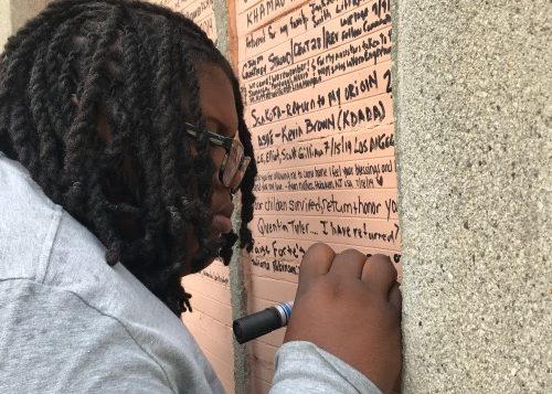 Tatiana Robinson writes a note in memory of her late grandfather on the Wall of Memory at the Assin Manso Slave River historical site in Ghana. This site was opened in 1994 to celebrate Emancipation Day when two enslaved descendant's bodies from the Diaspora (one from the U.S. and the from Jamaica) were brought back to Africa and buried.