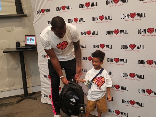 Washington Wizards star John Wall hands a backpack to Chase McKinney, 6, during the sixth annual John Wall Foundation back-to-school backpack giveaway at a Dave & Busters restaurant in Capitol Heights, Maryland, on Aug. 3. (William J. Ford/The Washington Informer)