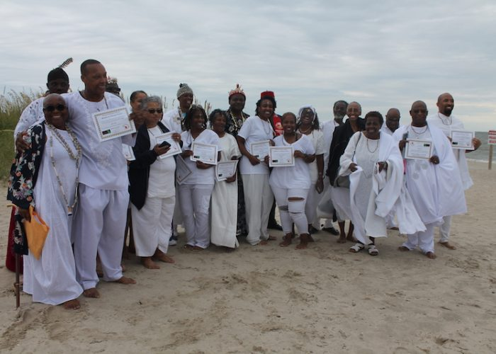 People hold their certificates with African names given to them during the African naming ceremony at Buckroe Beach on Aug. 24. (DR Barnes/The Washington Informer)