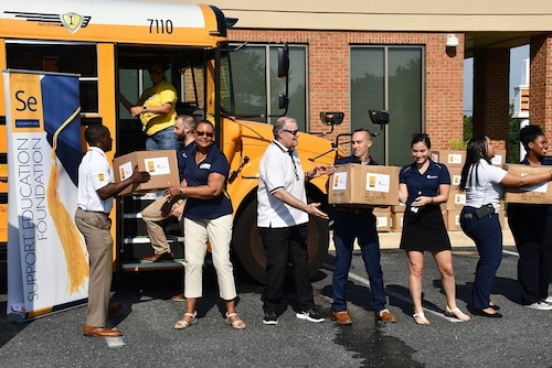 Employees for Educational Systems Federal Credit Union in Bowie and Prince George's County public school staff and volunteers form a line to load school supplies on a bus on Aug. 7. (Anthony Tilghman/The Washington Informer)