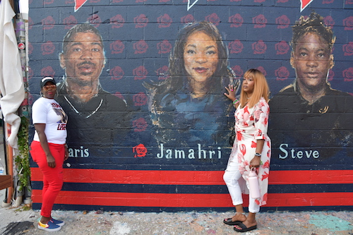 Seditra Brown stands by a portrait of her son Paris Brown as Q Wallace stands next to an image of her daughter Jamahri Sydnor. (Anthony Tilghman/The Washington Informer)