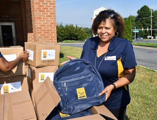 Victoria Samuels holds one of the 2,000 blue backpacks Prince George's County middle school students will receive before school starts Sept. 3. (Anthony Tilghman/The Washington Informer)
