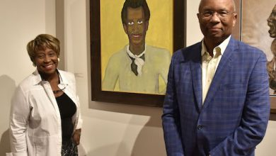 """Brenda and Larry Thompson of Atlanta with their [Un]Common Collection contribution by Beauford Delaney, """"Portrait #16,"""" at the Driskell Center at the Driskell Center at the University of Maryland on Sept. 19 (Robert Roberts/The Washington Informer)"""