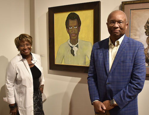 "Brenda and Larry Thompson of Atlanta with their [Un]Common Collection contribution by Beauford Delaney, ""Portrait #16,"" at the Driskell Center at the Driskell Center at the University of Maryland on Sept. 19 (Robert Roberts/The Washington Informer)"