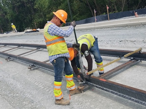 Construction workers lay down track for the Purple Line light-rail project, which will extend from New Carrollton in Prince George's County to Bethesda in Montgomery County, on Sept. 5. (William J. Ford/The Washington Informer)