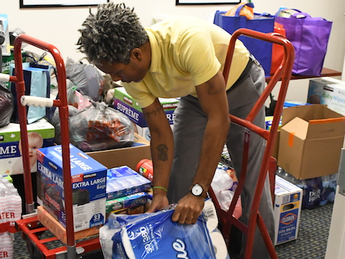 Felipe Mitjor, administrative assistant at the Bahamas Consulate, collects donations for victims of Hurricane Dorian at the Bahamas Embassy Consular Annex in northwest D.C. on Sept. 5. (Roy Lewis/The Washington Informer)