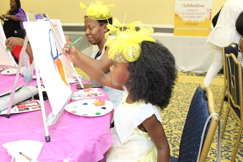 "EmauniJ Manley (foreground) paints a butterfly with her mother, Rosalynd Manley, at the ""Girls Talk: Love United"" Mother Daughter Tea at Camelot by Martin's in Upper Marlboro on Sept. 28. (Brigette Squire/The Washington Informer)"