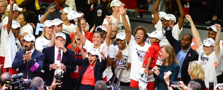 The Washington Mystics celebrate with the championship trophy after its 89-78 win in Game 5 of the WNBA finals at the Entertainment and Sports Arena in D.C. on Oct 10. (John E. De Freitas/The Washington Informer)