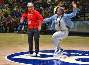 """Audience members compete in a """"beat-your-feet"""" contest during a Global Mixed Gender Basketball game between the Washington Fusion vs Chicago Vikings at the Entertainment and Sports Arena in southeast D.C. on Nov. 16. The league features both male and female players. (Brigette Squire/The Washington Informer)"""