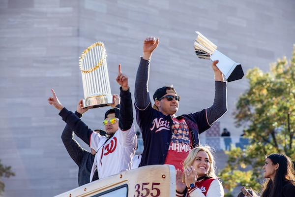 Washington Nationals first baseman Ryan Zimmerman (right) holds the National League Championship trophy with his wife seated by his side and the Nationals general manager Mike Rizzo hoists the World Series trophy during the Nationals' parade Nov. 2 in northwest D.C. (Ja'Mon Jackson/The Washington Informer)