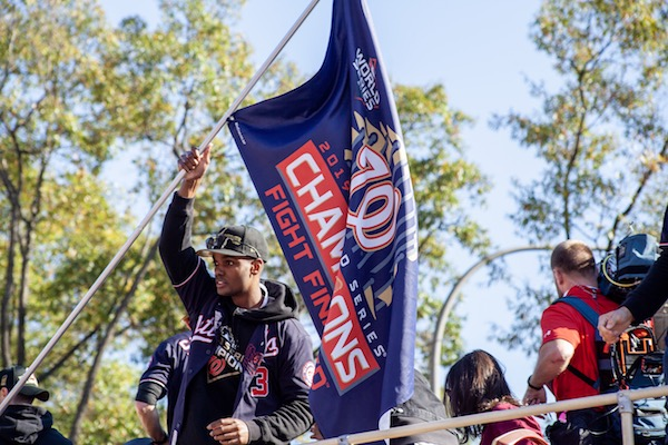 Washington Nationals center fielder Michael A. Taylor waves a flag during a Nov. 2 celebratory parade in northwest D.C. for the team's World Series win. (Ja'Mon Jackson/The Washington Informer)