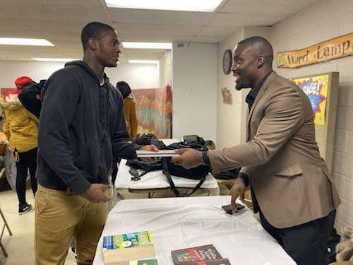 Entrepreneur and former NFL cornerback Vontae Davis gives a copy of his new children's book to Derrick Lewis during College Bound Inc.'s weekly academic mentoring session at Walker Memorial Baptist Church in northwest D.C. on Nov. 14. (Courtesy of Kenneth Ward)