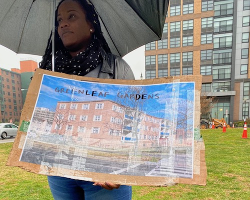 A member of the Right to DC campaign holds up a photo rendering of the Greenleaf Gardens Apartments during a December protest at the D.C. Housing Authority headquarters. (Courtesy of Alexis Mckenney)