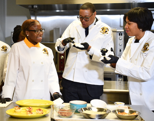 DCPS Chancellor Lewis Ferebee (center) and D.C. Mayor Muriel Bowser (right) sample some treats, courtesy of Ballou Senior High School students in the Southeast-based school's culinary arts academy. (Anthony Tilghman/The Washington Informer)