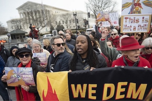 Joaquin Phoenix (center) and Dr. Omekongo Dibinga march Jan. 10 against the war in Iran at a rally where notably only a few African Americans attended. (Anthony Tilghman/The Washington Informer)