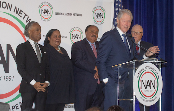 Former President Bill Clinton speaks as (from left) the Rev. Al Sharpton, Tanya Lombard and Martin Luther King III listen during the National Action Network's annual Dr. Martin Luther King Jr. Day Celebration Breakfast at the Mayflower Hotel in D.C. on Jan. 20. (Shevry Lassiter/The Washington Informer)