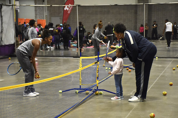 Washington Tennis Association representatives hold court with a young child during the NBC4/T44 Telemundo Health and Fitness Expo at the Walter E. Washington Convention Center, held Jan 18-19. (Robert R. Roberts/The Washington Informer)