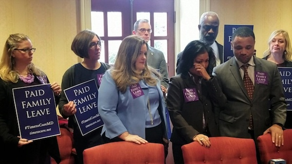 Del. Kris Valderrama (center) dabs her eye while giving emotional remarks Jan. 28 on legislation she will sponsor in the Maryland General Assembly to approve paid family leave for employees. (William J. Ford/The Washington Informer)