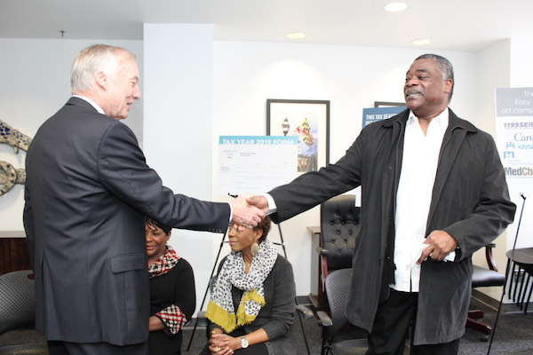 Baltimore Orioles legend Eddie Murray (right) shakes hands with Maryland Comptroller Peter Franchot before a Jan. 27 press conference in Baltimore to kick off opening day of the state's health insurance enrollment program. (Brigette Squire/The Washington Informer)