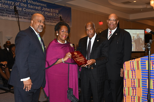 The Rev. Dr. Timothy Stewart (second right), president of the Progressive National Baptist Convention, standing with Rev. David R. People (left) and Dr. A. Wayne Johnson (right), presents Rep. Sheila Jackson Lee (D-Texas) with the MLK Award during the Progressive National Baptist Church Mid-Winter Board Meeting in San Antonio, Texas, on Jan. 20. (Roy Lewis/The Washington Informer)