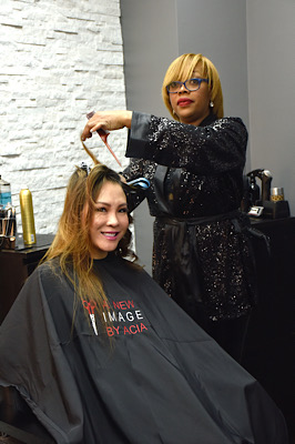 Acia Williams prepares model Mabel Lei's hair for upcoming event after receiving the hair salon as a gift from Chet Bennett. (Robert R. Roberts/The Washington Informer)