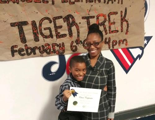 Owen Carpenter, a fifth grader at Hearst Elementary School, standing with his mother Shanta Mays-Carpenter, will be heading to the Washington Informer Charities Spelling Bee in a few weeks. (Courtesy of Ryan Garfield)