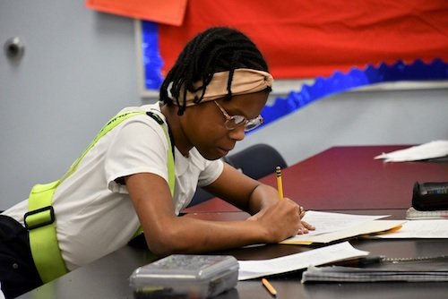 Jalah Berrian, a fifth grade student at William Beanes Elementary School in Suitland, jots down notes during a class discussion on climate change. (Anthony Tilghman/The Washington Informer)