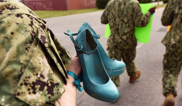 "A sailor from Navy Expeditionary Combat Command carries a pair of shoes, painted teal to symbolize victims of sexual assault, as she participates in the ""Walk a Mile in Their Shoes"" command event at Joint Expeditionary Base Little Creek on Aug. 25. (Mass Communication Specialist 3rd Class Lisa Reese/Navy via Military Times)"