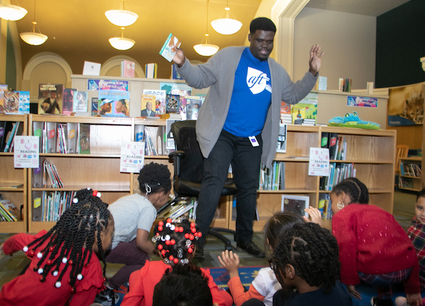 Branden Mitchell reads an interactive story to students during library time at Wheatley Education Campus in northeast D.C. (Shevry Lassiter/The Washington Informer)