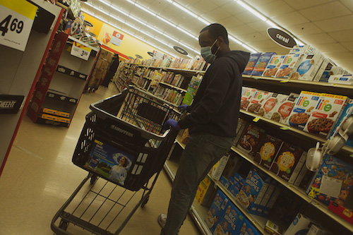 A patron at a local grocery chain dons hand protection and a mask while shopping. (Ulrich Fonou/The Washington Informer)