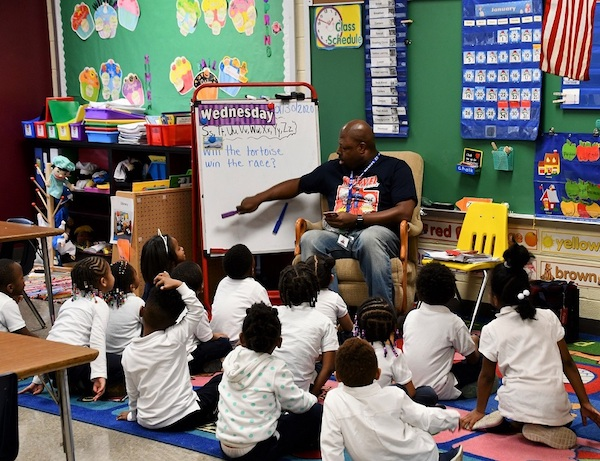 Antonio Logan, a pre-kindergarten teacher at William Beanes Elementary School in Suitland, helps students to learn words that begin with certain letters in the alphabet. (Anthony Tilghman/The Washington Informer)