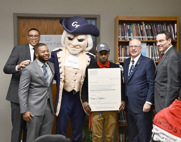 Youth scholar Michael Prather celebrates with city and school officials. (Anthony Tilghman/The Washington Informer)