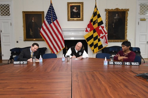 Maryland Gov. Larry Hogan (center) signs emergency legislation to combat the coronavirus in Annapolis on March 19. Alongside Hogan are Senate President Bill Ferguson (left) and House Speaker Adrienne Jones. (Courtesy of the governor's office)