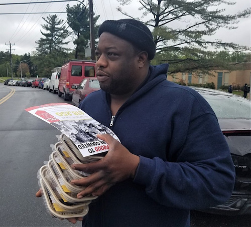 Gordan McKenzie of Beltsville, Maryland, holds eight food platters at the James E. Duckworth Regional Center during an event to distribute 1,000 meals amid the coronavirus pandemic on April 24. (William J. Ford/The Washington Informer)