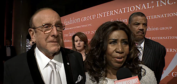 Clive Davis (left) and Aretha Franklin speak with Videofashion at the 30th Annual Night of Stars in New York City on Oct. 22, 2013, as Franklin's escort Willie Wilkerson (right) looks on. (Screen grab courtesy of Videofashion)