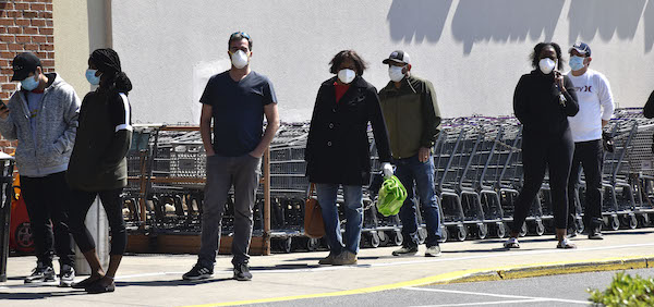 Shoppers wear masks as required by government officials in Montgomery County as they line up to enter a grocery store. (Robert R. Roberts/The Washington Informer)
