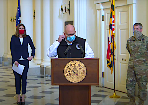 Maryland Gov. Larry Hogan removes a mask as he prepares to give an update of the state's response to the coronavirus pandemic during a press conference in Annapolis on April 10.