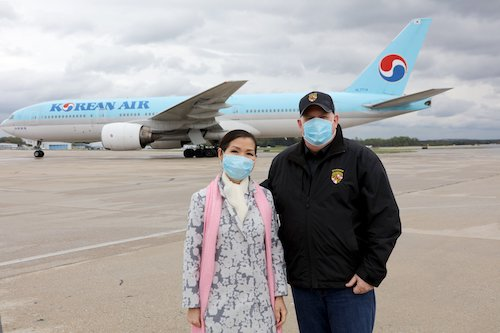 Maryland Gov. Larry Hogan (right) and wife Yumi stand on the tarmac at Baltimore-Washington International Thurgood Marshall Airport to welcome a Korean Air passenger plane delivering 500,000 coronavirus tests from South Korea. (Courtesy of Governor's Office)