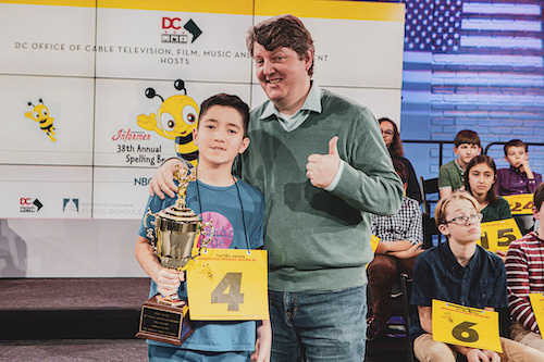 Biko Sheridan, 11, a fifth-grade student at Mundo Verde Public Charter School in Northwest, with his dad Chris, celebrate winning Washington Informer Charities' 38th annual Spelling Bee held at the Office of Cable Television, Film, Music and Entertainment (OCTFME) in Northwest on February 29. The Spelling Bee was televised on April 19. (Ulrich Funoa/The Washington Informer)