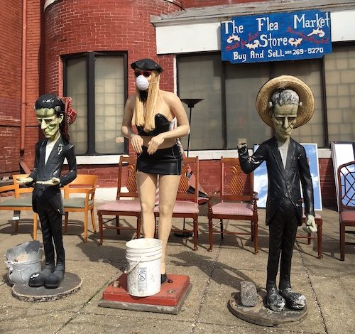 A flea market in northeast D.C. promotes coronavirus safety by staging three mannequins, including one wearing a mask. (Roy Lewis/The Washington Informer)