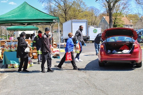 """Seat Pleasant city employees, members of SHABACH! Ministries and volunteers load grocery bags into vehicles during """"grab and go"""" grocery giveaway on April 2. (Brigette Squire/The Washington Informer)"""