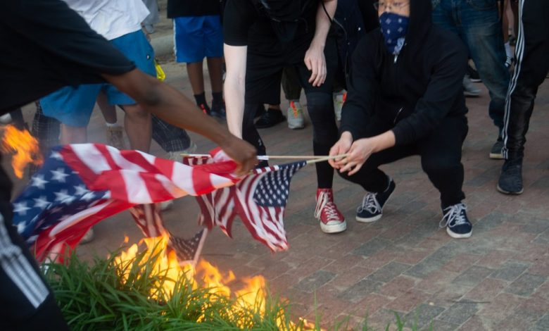 Protesters set fire to American flags outside the White House on May 29, 2020, in a solidarity rally for activists in Minneapolis who are rioting after the death of black man George Floyd in police custody. (Ford Fischer/Zenger)