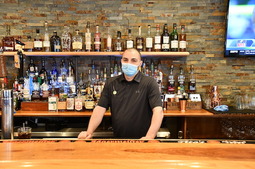 Nadol Hishmeh stands behind the bar at Olive on Main, a restaurant he co-owns with his brother in Laurel, Maryland. (Anthony Tilghman/The Washington Informer)
