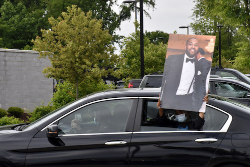 A protester holds out a photo of Finan Berhe, killed May 7 in White Oak by Sgt. David Cohen, a member of the Montgomery County Police Department. (Robert R. Roberts/The Washington Informer)