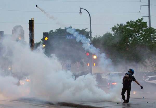 A protester throws a gas canister back at police during a protest over the killing of George Floyd in Minneapolis on May 26, 2020. (Chris Juhn/Zenger News Service)
