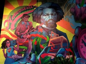 A mural by local artist Aniekan Udofia showing Chuck Brown, Frederick Douglass and the Big Chair is on display at the new Starbucks in the Anacostia neighborhood of southeast D.C. (John Muller/Special to The Informer)